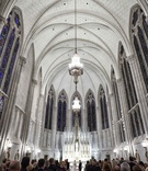 Rounded vaulted ceiling and chandeliers at St James Chapel in Chicago wedding venue stained glass