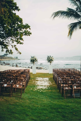 beach ceremony space destination wedding punta mita mexico wood chairs grass petals arrangements
