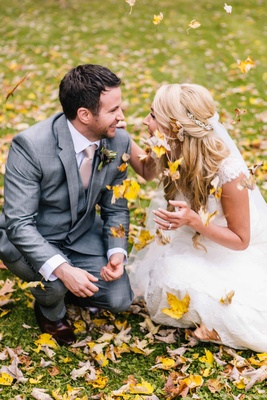 bride and groom knell in fall leaves and throw leaves in the air