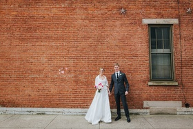 bride in a-line wedding dress holds hands with groom in grey suit in front of brick wall