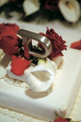 White cake with metal silver letter on top with red roses