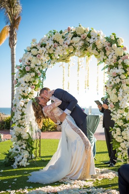 newlywed couple dip kiss outdoor ceremony flowers garden wedding beach floral arch slit dress ca