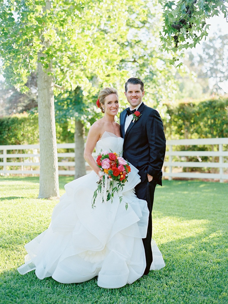 Bride in strapless Vera Wang wedding dress with vibrant pink and red bouquet with groom in tuxedo