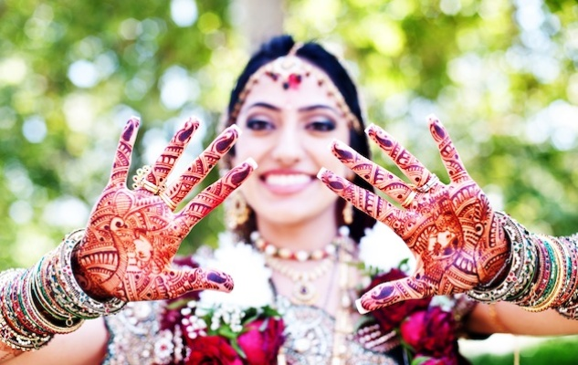 Indian bride wearing bangles and henna on hands