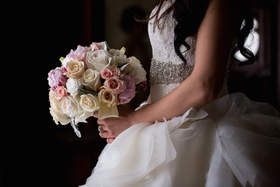 Bride in a strapless Lazaro dress with lace bodice, ruffled skirt, pink & white rose bouquet