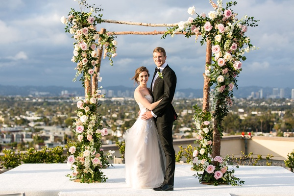 wedding ceremony on rooftop overlooking los angeles bride in strapless wedding dress with tall groom