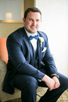groom in navy joseph abboud suit, blue bow tie, black watch