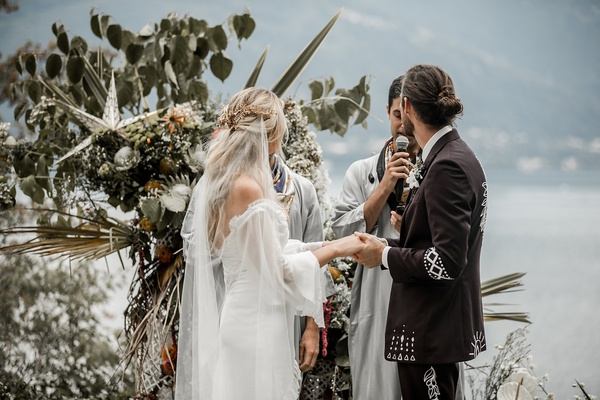 bride and groom at boho chic wedding ceremony lake como star decor palm protea flowers