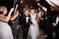 a bride and groom make their grand exit from their reception while guests wave sparklers
