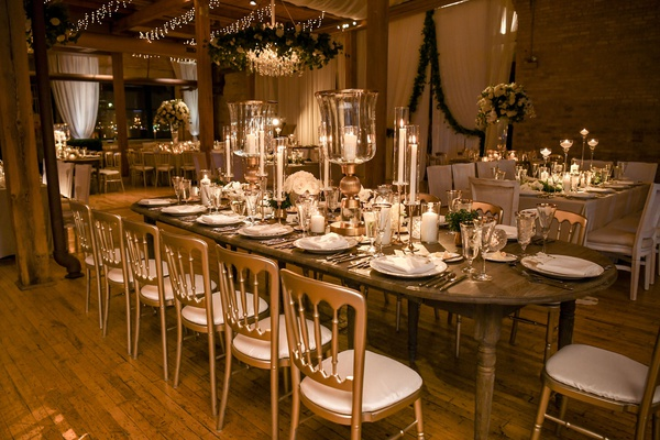 wedding reception wood table taper candle candleabra chandelier wreath of greenery rustic chic
