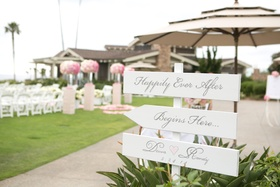 White wood arrows pointing toward wedding ceremony