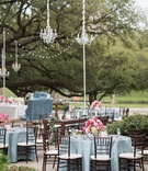 chandeliers hanging from trees for outdoor reception blue linens chiavari chairs