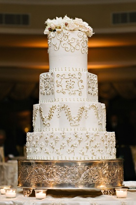 White wedding cake round hexagon layers flowers vines and flowers on top