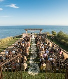 Grass lawn ceremony with ocean views and gated entry