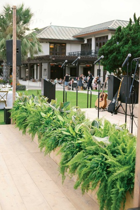 wedding reception live band stage greenery ferns tropical leaves in front of stage