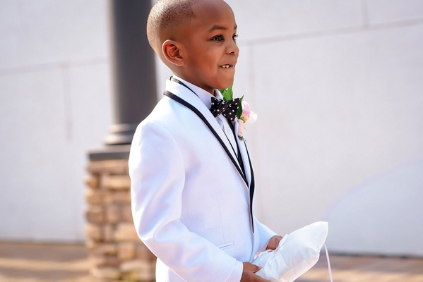 ring bearer walking down aisle with white ring pillow polka dot bow tie white jacket suit