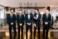 groom in tuxedo, groomsmen in suits and ties, and best man in tux and navy blue bow tie