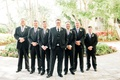 groom in three piece suit with circle boutonniere groomsmen in suits with lavender purple ties