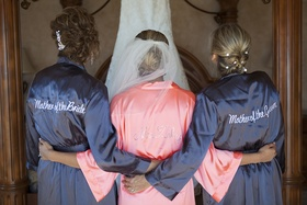 Bride wearing personalized pink robe with mother of bride and mother of groom personalized grey robe