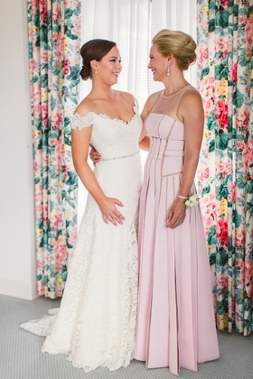 Bride in Legends Romona Keveza lace wedding dress and mother of bride in pleated illusion neckline