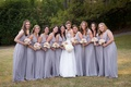 Bride holding white flowers with bridesmaids