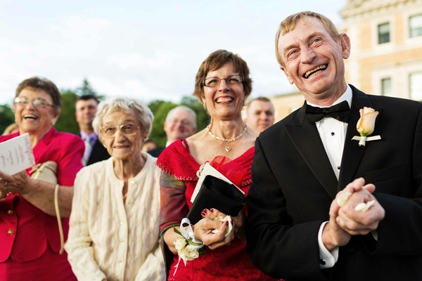 Groom's father dressed in a black tuxedo and mother in a red dress