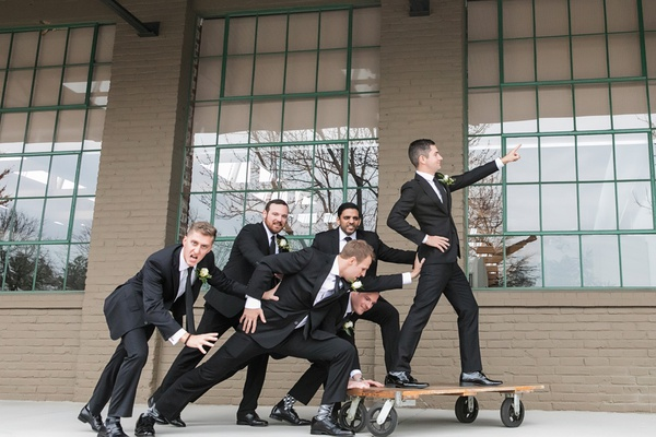 groom and groomsmen in black suits playful pose riding on dolly