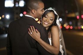 Bride in lace veil hugging groom in New York City