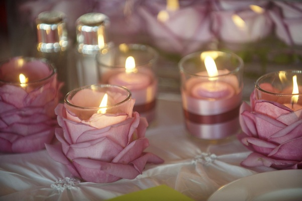 Small candleholders decorated with purple petals
