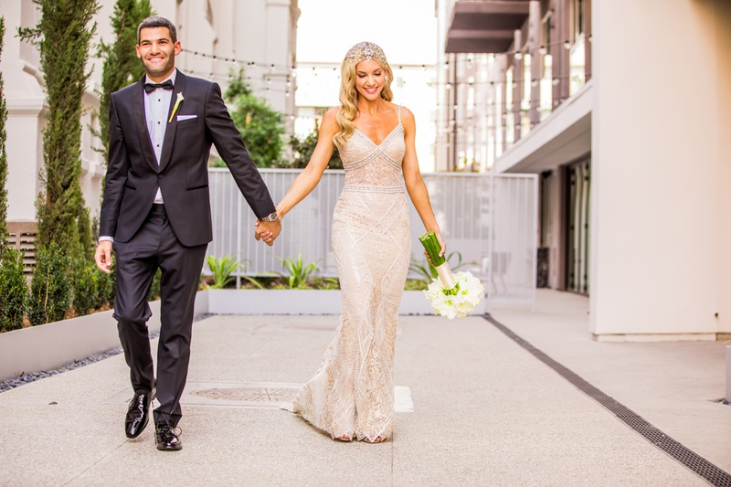 bride in berta bridal gown and jewel headpiece holds hands with groom in tuxedo