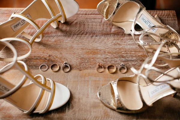 Brides' shoes lay next to wedding and engagement rings