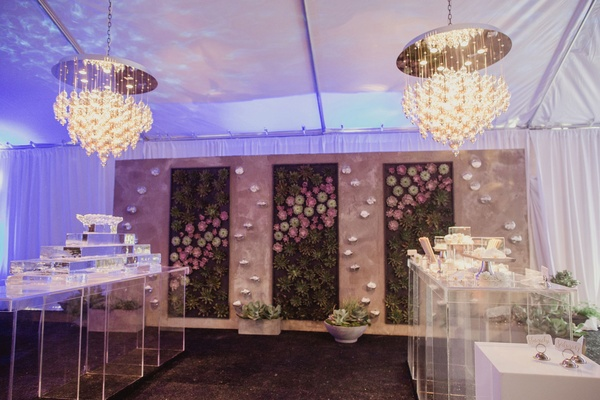 wedding reception food station with succulent wall and modern chandeliers