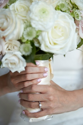 bride with solitaire engagement ring and baby pink bridal nails holding white bouquet