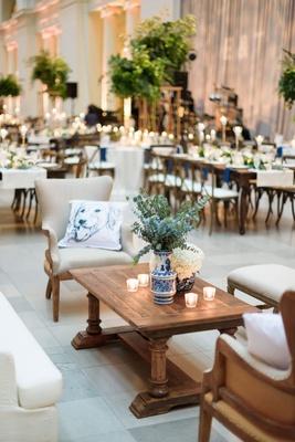 wedding reception lounge wood coffee table upholstered chair sofa blue white vase eucalyptus