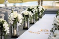 White aisle runner with antler monogram lined with lanterns candles white flowers greenery