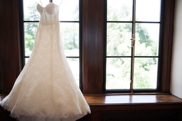 a bride's gorgeous gown with a modified a-line skirt and corset top hung up