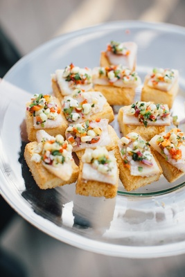 Wedding reception cocktail hour food crostini bread with slice of meat or cheese and fresh corn sals