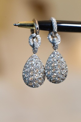 Diamond chain link earrings hanging from ball point pen