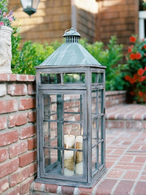 Rustic large lantern on brick steps with candlelight coming from white candles wrapped in gold