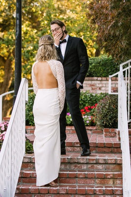 groom's cute reaction to first look, bride in open back wedding dress, lace long sleeves crepe skirt