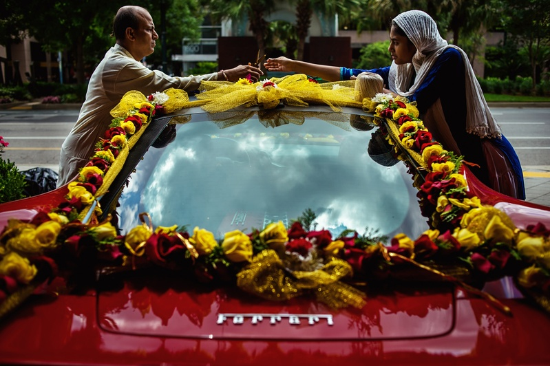 Red ferrari adorned with garlands of roses