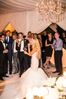 Bride in mermaid dress by galia lahav singing at reception as guests take photos on their phones