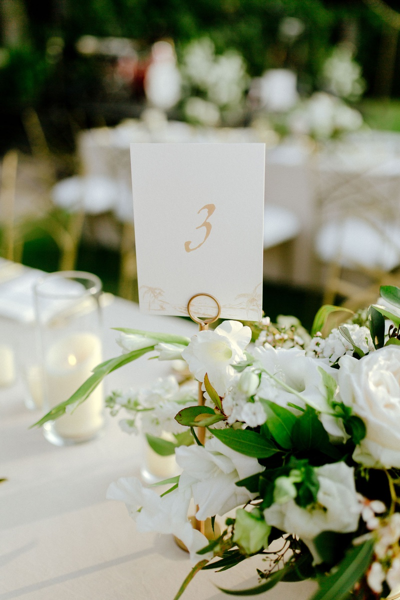 outdoor destination wedding reception tropical hawaii decor white flowers greenery gold table number