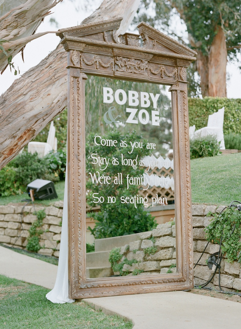 White text on large free-standing mirror at wedding ceremony