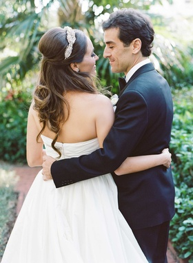 Bride in strapless Reem Acra a line wedding dress hugs groom with one arm headpiece half up hair