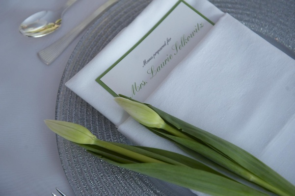 Two closed tulip flowers on top of green menu card