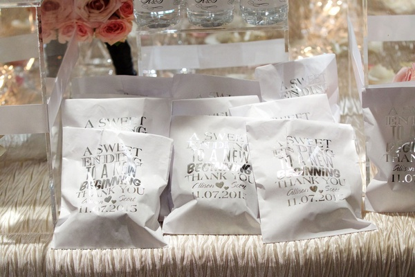 White wedding favor bags with silver lettering filled with sweet treats donuts dessert favor ideas