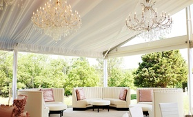 Ivory booths in lounge area at tent wedding