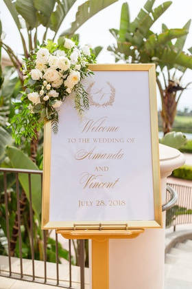 wedding welcome sign in gold frame with flower arrangement in the corner