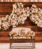 reclaimed wood wall with flower wall decor sweetheart table settee with white pink flowers